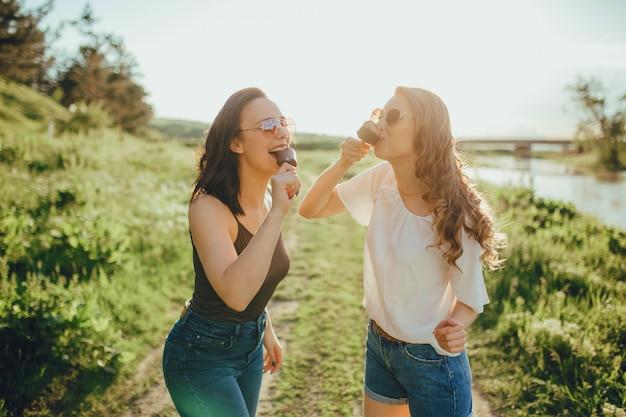 Две счастливые девушки, едят мороженое, летом тепло и весело, в очках, в белой и черной рубашке. на закате, позитивное выражение лица, на улице