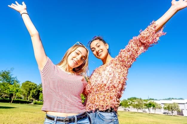 都市公園のフィールドを見て微笑んで両手を広げて抱き合っている2人の幸せな女の子