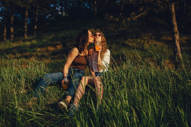 Two happy girls have fun, sit down on the grass, kiss on the cheek, drink cocktail in sunglasses, at sunset, positive facial expression, outdoor