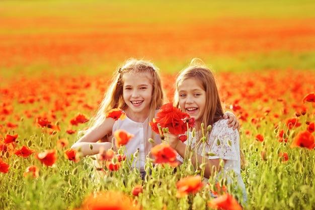 ケシのフィールドで楽しんでいる2つの幸せな女の子