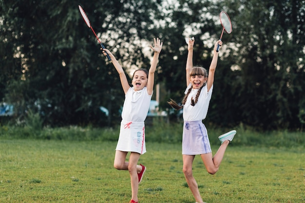 Two happy girls holding badminton jumping in the park with joy