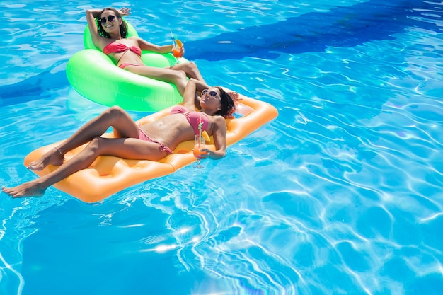 Две счастливые девушки держат коктейли и лежат на надувном матрасе в бассейне