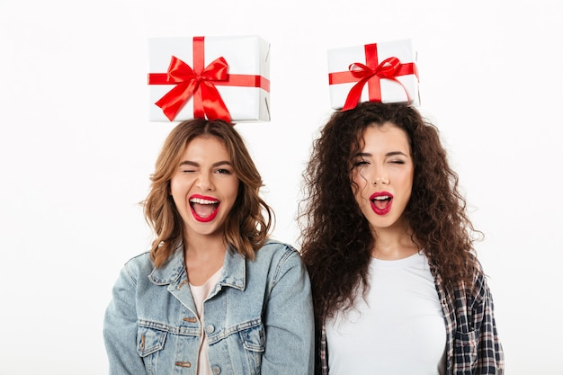 Two happy girls holding gifts on their heads while winks at the camera over white wall