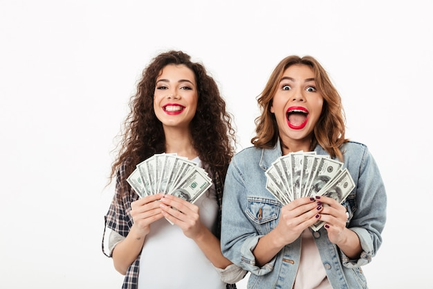 Two happy girls holding money and rejoices  over white wall