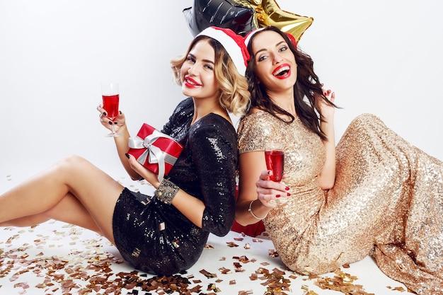 Две счастливые девушки в красной рождественской шляпе санта-клауса сидят на полу, пьют вино, смеются, наслаждаются временем вместе. в блестящем черно-золотом вечернем платье.