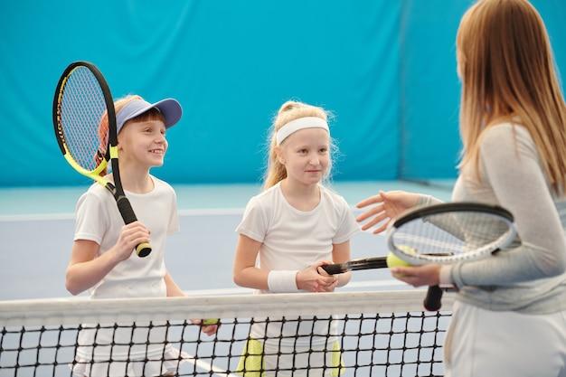 彼女の前でネットのそばに立って、彼女の言うことを聞いている間、女性のトレーナーを見ている白いスポーツウェアの2人の幸せな女の子
