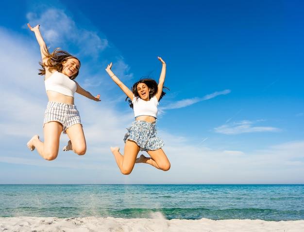 여름 휴가를 즐기는 열대 해변에서 함께 점프하는 두 명의 행복한 소녀