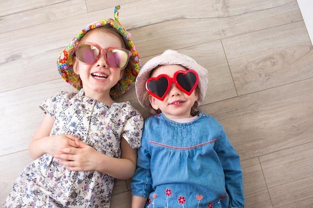 2人の幸せな女の子がサングラスと帽子をかぶって背中の床に横たわって笑う