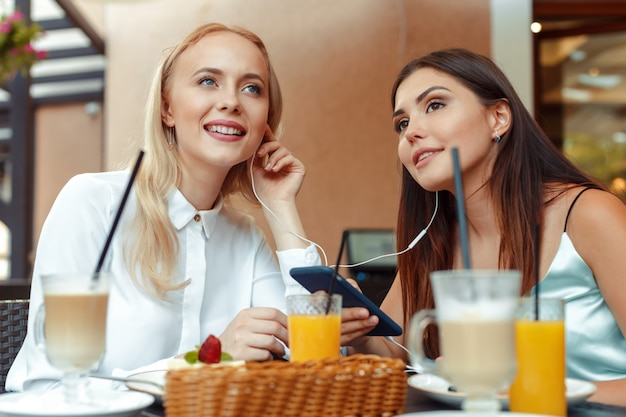 Two happy girls listening to music with shared earphones together in nice cafe