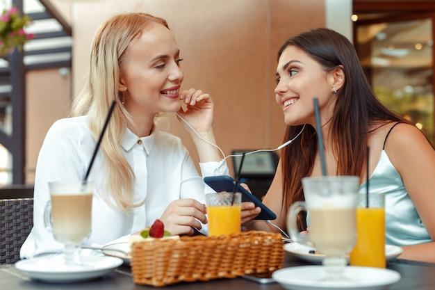 素敵なカフェで一緒にイヤホンを共有して音楽を聴く2人の幸せな女の子。音楽とエンターテイメントを楽しむ