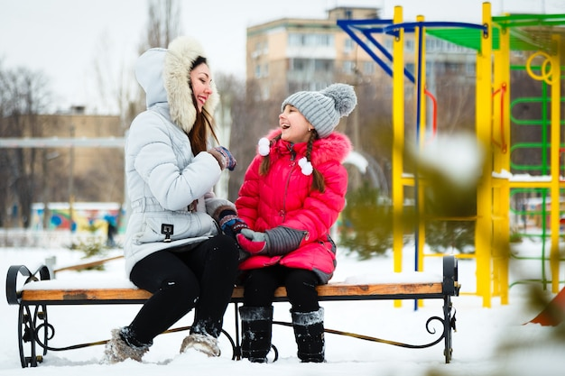 Two happy girls, mother and daughter sitting on a bench on a  playground in city park.