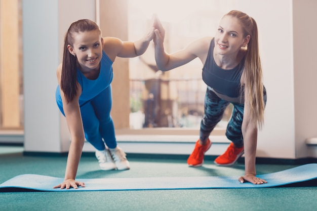 Two happy girls perform sports exercise at workout