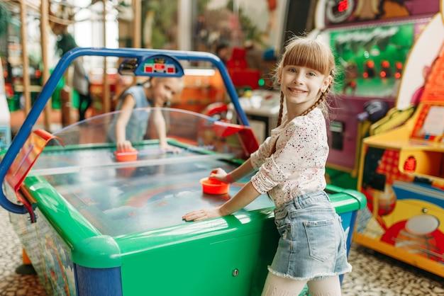 Две счастливые девушки играют в воздушный хоккей в игровом центре