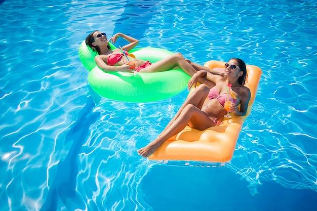 Две счастливые девушки отдыхают на надувном матрасе в бассейне с коктейлями