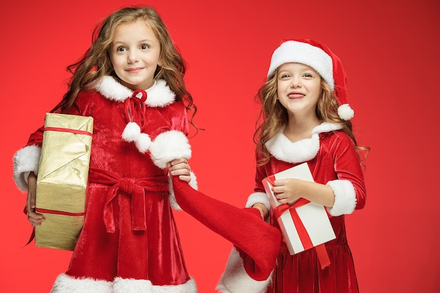 Two happy girls in santa claus hats with gift boxes at red studio