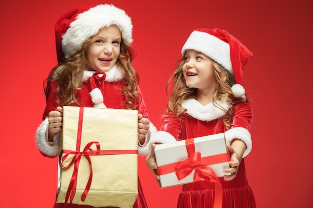 Two happy girls in santa claus hats with gift boxes on red