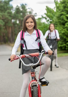 Two happy girls in school uniform riding on bicycles at morning