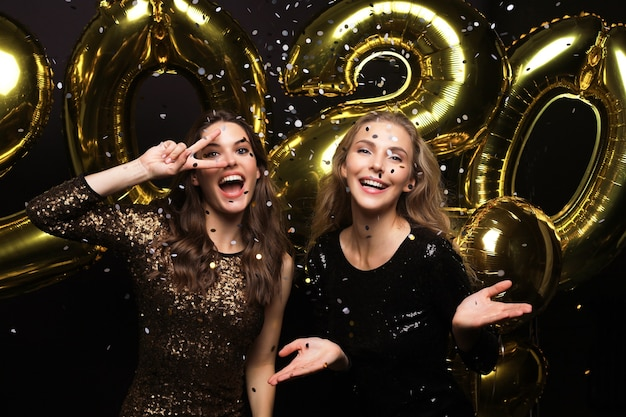 Two happy girls in shiny dresses posing while standing with gold colored 2020 number balloons on black background.