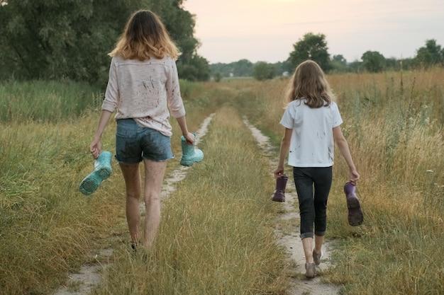 レインブーツを手に歩いて2つの幸せな女の子姉妹