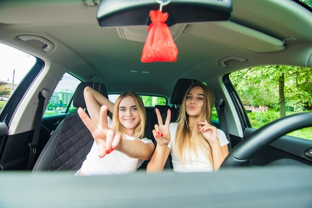 Two happy girls sitting in the car and gesturing victory sign have fun while having car trip
