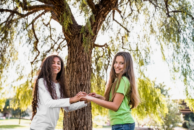 Two happy girls standing in front of tree holding each other's hands