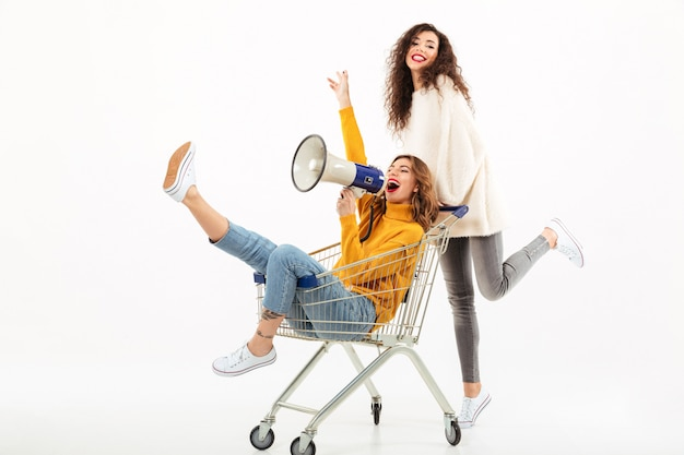 Two happy girls in sweaters having fun with shopping trolley and megaphone over white wall