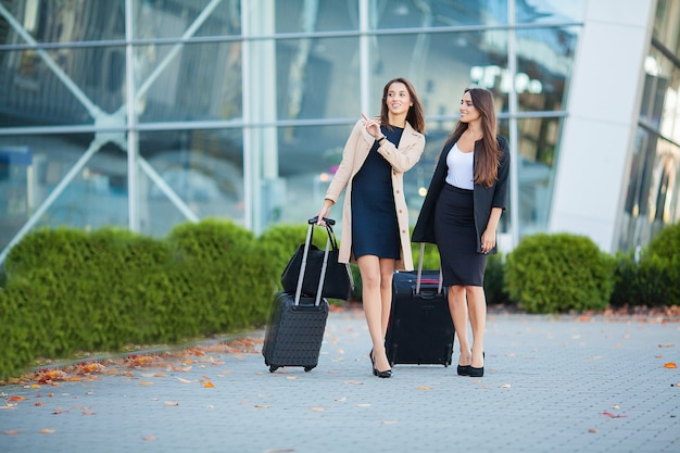 Two happy girls traveling abroad together, carrying suitcase luggage in airport