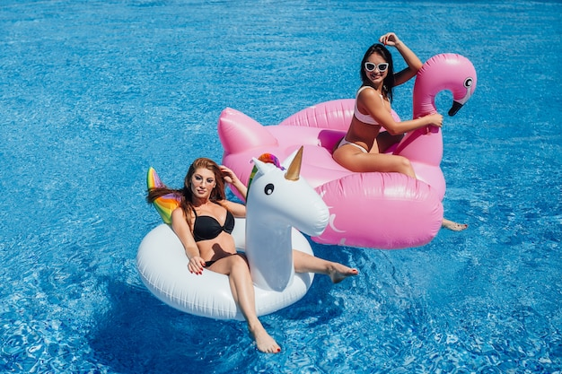 Two happy girls with beautiful figures on inflatable flamingos and unicorns in the pool
