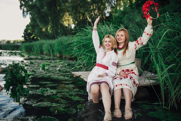 Две счастливые девушки с ногами в воде