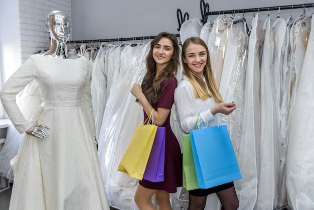 Две счастливые девушки с хозяйственными сумками в свадебном салоне