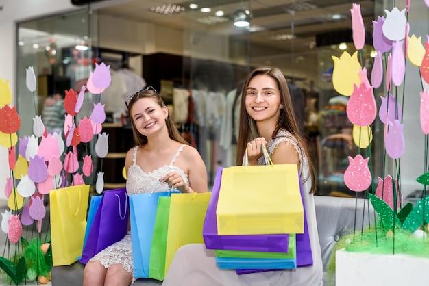 Две счастливые девушки с хозяйственными сумками позируют в торговом центре