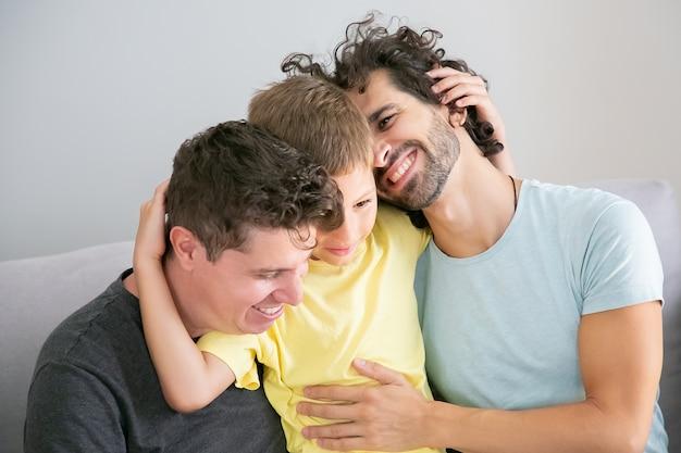 Due bei padri e figlio felici che si siedono sul divano insieme e si abbracciano. famiglia felice e concetto di genitorialità