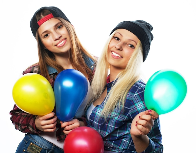 Две счастливые хипстерские девушки улыбаются и держат цветные воздушные шары на белом фоне