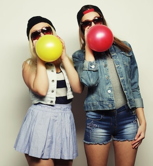 白い背景の上に色の風船を笑顔で保持している2人の幸せな流行に敏感な女の子