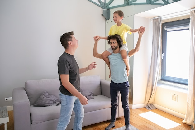 Due padri omosessuali felici e figlio che si divertono a casa, ragazzo cavalcando il collo dell'uomo e ridendo. famiglia e concetto di genitorialità