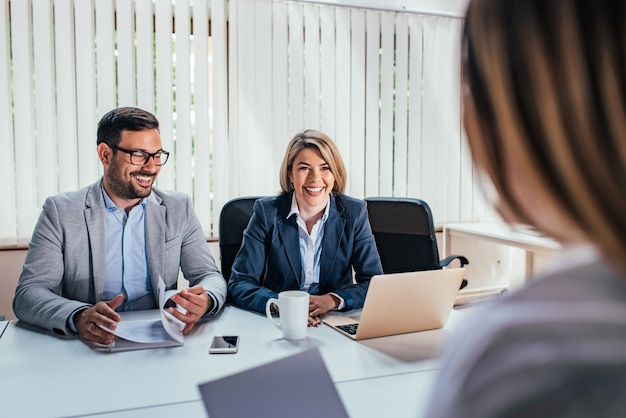 Two happy hr managers having interview with candidate.
