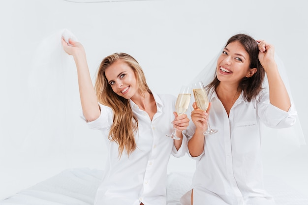 Two happy joyful girls having pre wedding party with glasses of champagne