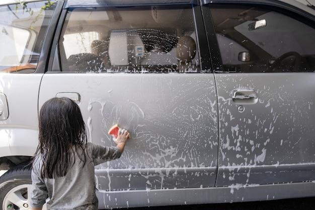 Два счастливых ребенка моют машину папы дома