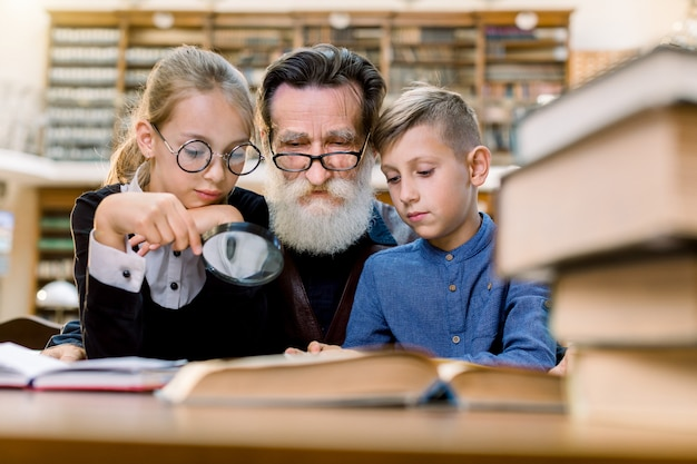 Two happy kids, boy and girl with magnifying glass glass listening to interesting book story from their handsome bearded grandfather or school teacher, sitting together in old library.
