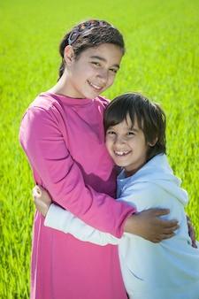緑の小麦の2人の幸せな子供たち