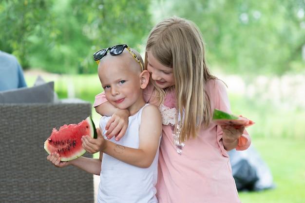 행복한 두 아이 - 집 뒤뜰의 나무 테라스에서 수박을 먹는 어린 소년과 소녀