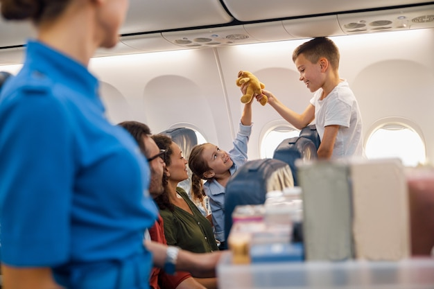Two happy kids playing with a toy during flight. family traveling together by plane. vacation, travel, airline, service concept