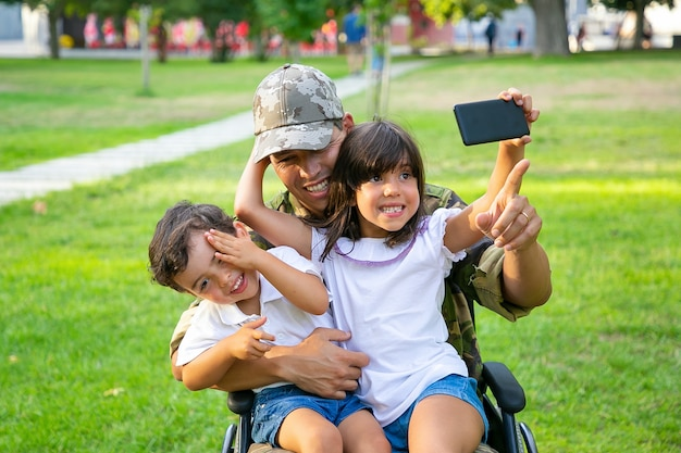 Two happy kids sitting on dads lap and taking selfie on cell. disabled military man walking with kids in park. veteran of war or disability concept