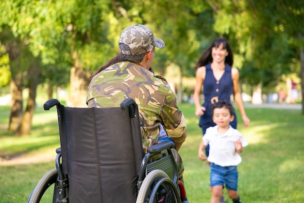 Two happy kids and their mom running toward disabled retired military father and hugging him. veteran of war or returning home concept