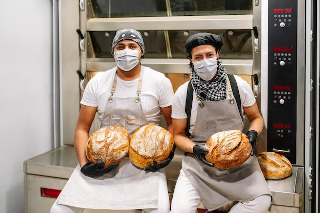 Two happy latino bakers showing how they made a loaf of wheat bread in the bread oven with gloves on their hands and masks on their faces