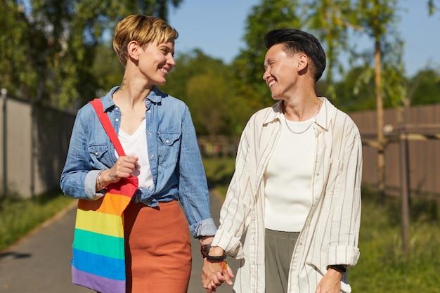 通りを歩きながら笑顔で話し合う2人の幸せなレズビアン
