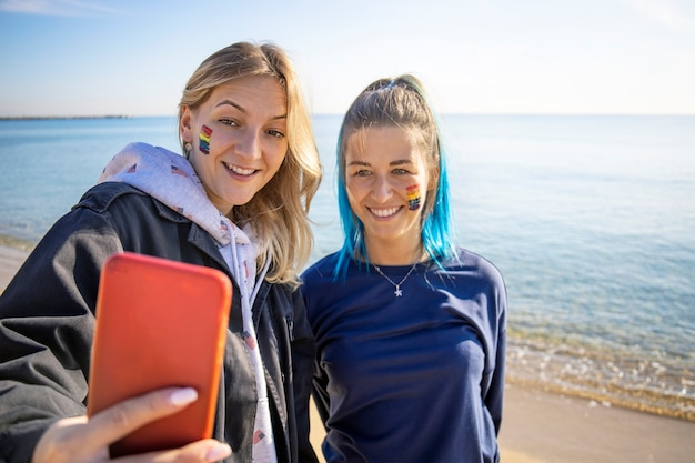 Two happy lgbt girlfriends taking selfie on the beach. rainbow homosexual flag sign on face