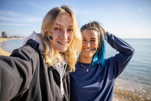 Two happy lgbt girlfriends taking selfie on the beach