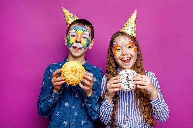 2人の幸せな小さな親友は、紫色の壁に分離されたドーナツを保持している誕生日の帽子を着用します