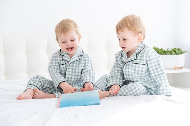 Two happy little boys brothers twins in pajamas reading book i